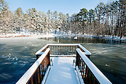 A snow covered dock over a partially frozen pond in Roland, Arkansas.