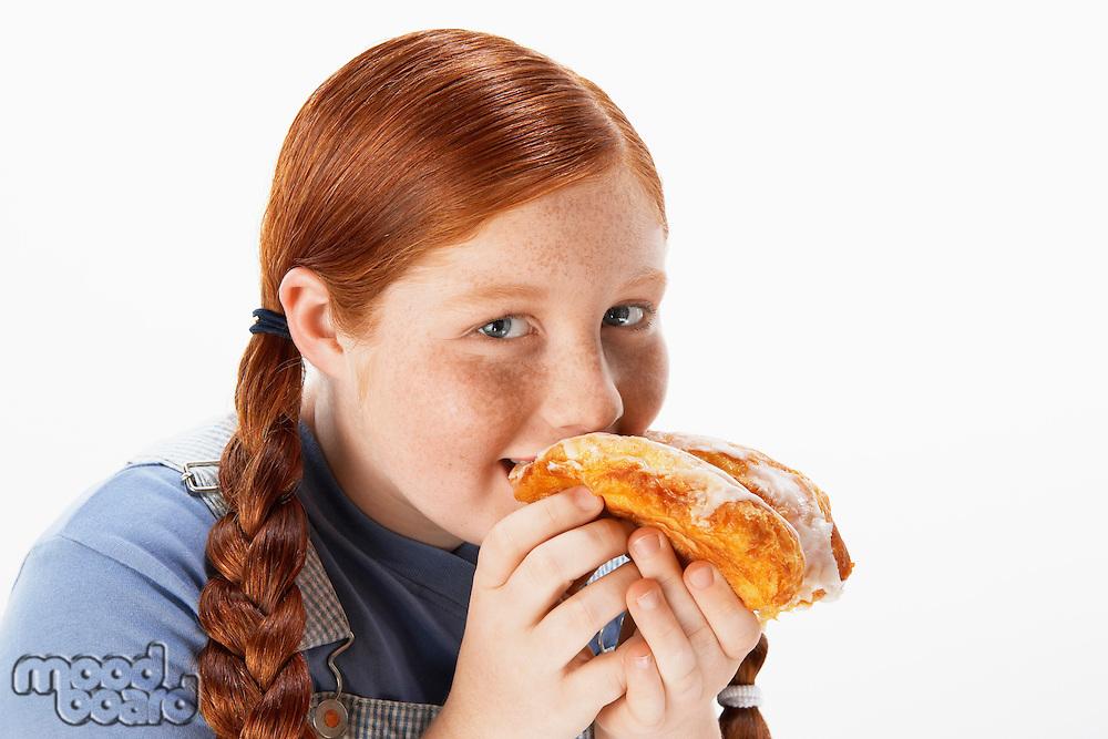 Overweight girl (13-15) eating doughnut portrait
