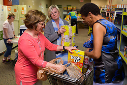 Keeneland employee Amy Petit, left and Amy Gregory, center, guide Barbara Turley of Lexington through her food distribution day at a God's Pantry Distribution site, Tuesday, April 18, 2017 at Broadway Christian Church in Lexington.