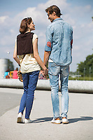 Young couple looking at each other while holding hands on street