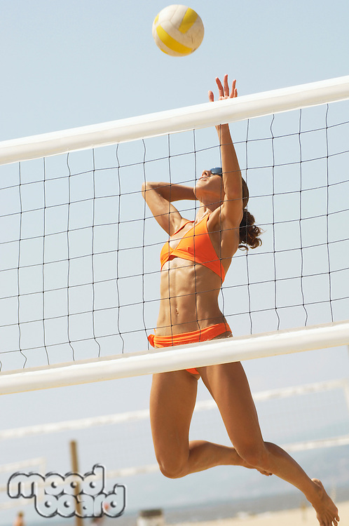 Female beach volleyball player jumping to spike volleyball over net