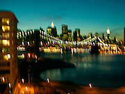 Blurry view of the Brooklyn Bridge and downtown Manhattan by night.