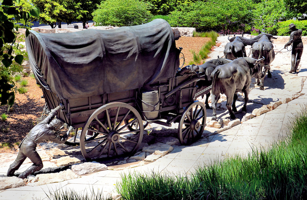Bronze of Wagon Train at Pioneer Courage Park in Omaha, Nebraska<br /> Across six blocks in downtown Omaha, Nebraska, are more than 120 bronze sculptures in Spirit of Nebraska&rsquo;s Wilderness and Pioneer Courage parks.  This 12 foot high, covered wagon that&rsquo;s stuck in a dry creek bed is one of four pioneer families heading west on May 21, 1841.  The elaborate sculptures by Blair Buswell and Ed Fraughton are exquisitely detailed and are 1 &frac12; times life size.  The project was sponsored by First National Bank.