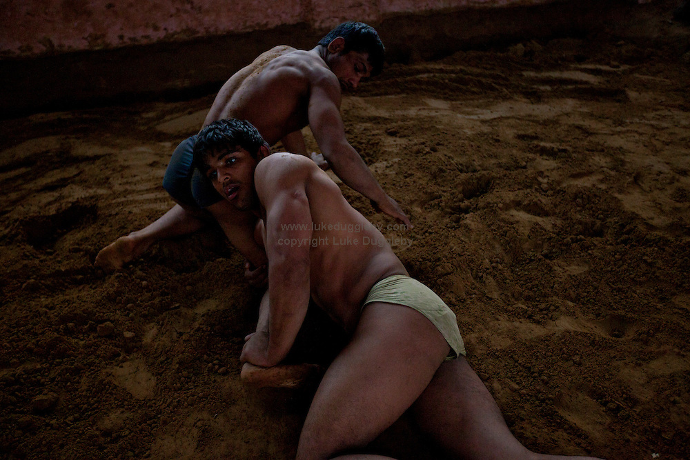 Wrestlers fight on the traditional soil ring. For almost 3000 years loincloth clad duels on mud have transfixed spectators across India. Yet wrestling in India is a sport in transition. In 2004 the Indian Fighters Federation tried to prohibit the practice of traditional mud wrestling, claiming that for India to compete at an international level fighters must train using mats. Whilst competing on mud can earn good money for a wrestler at events called dungals in India's countryside, the techniques are starkly different. ..The Guru Hanuman Akhara, a wrestling school in Old Delhi, is the epicentre of this ancient wrestling tradition as it begins to enter the modern world. Now training fighters on both mats and mud the school has produced hundreds of champions at both domestic and international level...Established in 1925, making it the oldest in India, it was in 1955 that Vijay Pal, or Guru Hanuman as he later became known, took over the coaching...Born to a poor family in the desert state of Rajasthan he chose never to marry and instead dedicated his whole life to wrestling, becoming a legend, who created a model for modern Indian wrestling by combining traditional Indian wrestling called Kushti with international standards. His statue and mausoleum stands overlooking the outer courtyard of the school.....