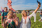 Time for selfies as the sun comes out at the end of the afternoon in the avenue of flags near the Other Stage - The 2017 Glastonbury Festival, Worthy Farm. Glastonbury, 2 June 2017