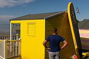 A man stands next to a bright yellow beach hut and waits patiently for his family to come along on the seafront promenade at Whitstable, on 18th July 2020, in Whitstable, Kent, England.