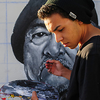 072314  Adron Gardner/Independent<br /> <br /> Artist Greg Ballenger paints a mural of his uncle Eugene Attcity on the stucco wall of Fitz Sergent's home in Gallup Wednesday.