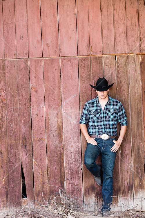 cowboy leaning against a rustic barn on a ranch