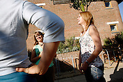 Helen Vincent, (left) and Hayley Bell, (right) working for Bio Regional Development Group are having some time off work in the BedZED housing complex on Thursday, Sep. 6, 2007, in London, UK. BedZED or the Beddington Zero Energy Development, is an environmentally-friendly housing development near Wallington, England in the London Borough of Sutton. It was designed by the architect Bill Dunster who was looking for a more sustainable way of building housing in urban areas in partnership between the BioRegional Development Group and the Peabody Trust. There are 82 houses, 17 apartments and 1,405 square meters of work space were built between 2000. The project was shortlisted for the Stirling Prize in 2003. The project is designed to use only energy from renewable source generated on site. In addition to 777 square meters of solar panels, tree waste is used for heating and electricity. The houses face south to take advantage of solar gain, are triple glazed and have high thermal insulation while most rain water is collected and reused. Appliances are chosen to be water efficient and use recycled water wherever possible. Low impact building materials were selected from renewable or recycled sources and were all originating within a 35 mile radius of the site to minimize the energy required for transportation. Also, refuse collection facilities are designed to support recycling and the site encourage eco-friendly transport: electric and LPG cars have priority over petrol/diesel cars, and electricity is provided by parking spaces appositely built for charging electric cars.