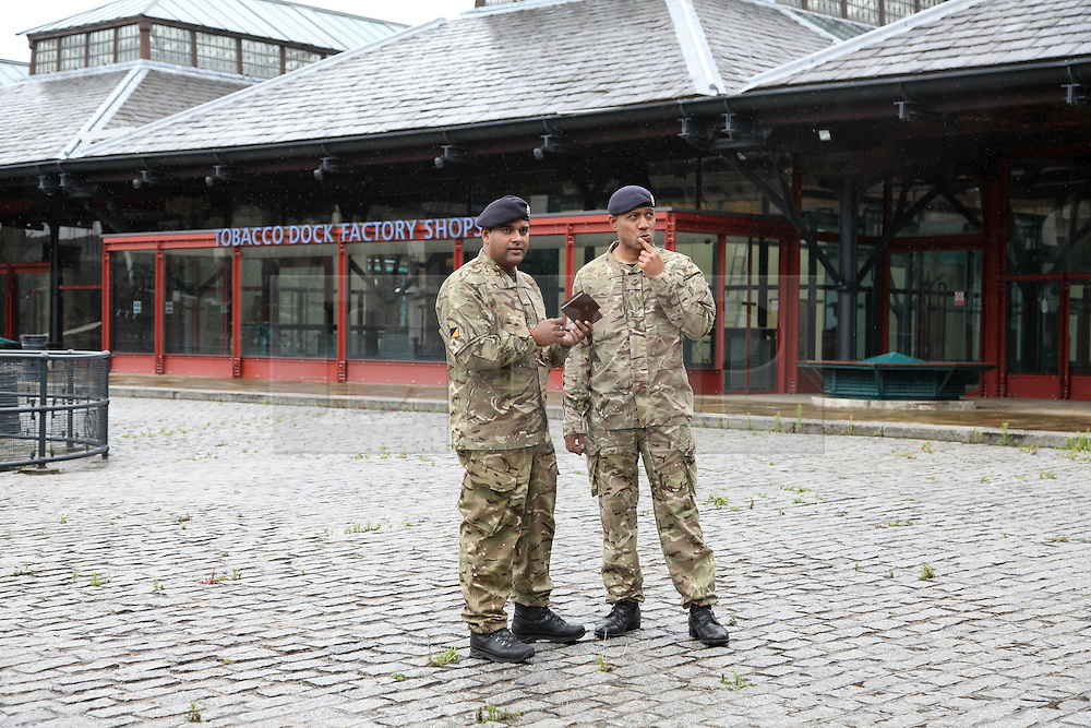 © Licensed to London News Pictures. 16/07/2012. London, UK. Two members of the British military at Tobacco Dock in London E1. The Grade 1 listed warehouse has been shortlisted by the Ministry of Defence to provide accommodation for the 3,500 extra troops being drafted in to provide security at the Olympic Games. An announcement confirming the temporary military camp at Tobacco Dock is expected in the House of Commons later today, 16 July 2012.. Photo credit : Vickie Flores/LNP