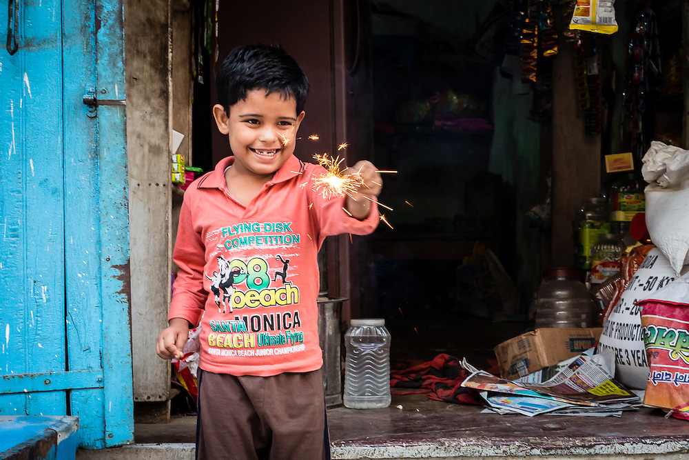 This kid was lighting a small candle for Diwali, the Hindu Festival of Lights. Light candles and setting up firecrackers are obligatory tasks in the celebrations of Diwali.