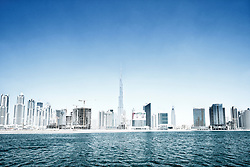 View of modern skyline of Business Bay district under construction with Burj Khalifa to rear in Dubai United Arab Emirates