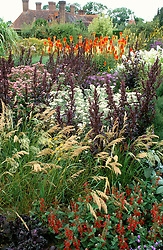 Looking towards the house from the High Garden at Great Dixter - Stipa splendens, Atriplex hortensis, Kniphofia uvaria 'Nobilis' & Anaphalis margaritacea (A.yedoensis)