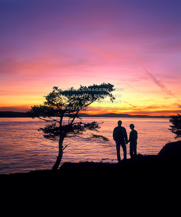Image of a couple at Shark Reef Park at sunset, Lopez Island, San Juans, Washington, Pacific Northwest, model released