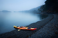 Red kayak on the Salish sea shore in yearly morning mist. Nanaimo, Vancouver Island, British Columbia, Canada.