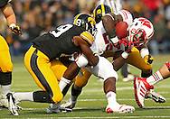 November 02 2013: Wisconsin Badgers running back Melvin Gordon (25) fumbles the ball as he is hit by Iowa Hawkeyes defensive back B.J. Lowery (19) and Iowa Hawkeyes defensive back John Lowdermilk (37) during the first half of the NCAA football game between the Wisconsin Badgers and the Iowa Hawkeyes at Kinnick Stadium in Iowa City, Iowa on November 2, 2013. Wisconsin defeated Iowa 28-9.