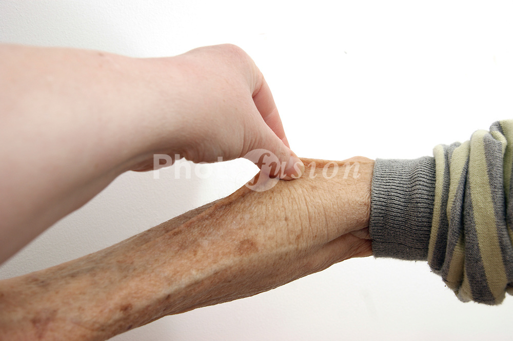 Elderly woman having forearm pinched to illustrate a Skin Turgor (this picture represents the patient is dehydrated) model released
