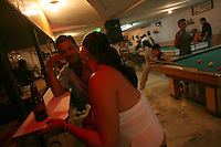 A man chats with a woman at a bar in Leiva, a small remote village in the southern Colombian state of Nariño, on June 24, 2007. Leiva has long been a coca village; most of the people who live in the area have long relied on the coca business in order to make ends meet. But with increasing pressure by the Colombian government, with fumigation and manual eradication of the coca fields, many people are now trying to figure out what the will do if they can?t rely on their meager coca profits. (Photo/Scott Dalton)