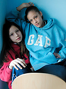 Two girls, one wearing a Gap jumper and a chain with the letter 'D'