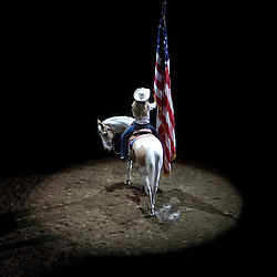 Former Miss Rodeo America 1999 Shelly Williams holds the American Flag in a spotlight at the start of the Snake River Stampede in Nampa. Saturday July 20, 2013