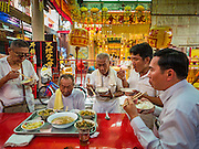 04 OCTOBER 2016 - BANGKOK, THAILAND: Temple volunteers, all dressed in white, eat a vegetarian dinner during the Vegetarian Festival at the Chit Sia Ma Chinese shrine in Bangkok. The Vegetarian Festival is celebrated throughout Thailand. It is the Thai version of the The Nine Emperor Gods Festival, a nine-day Taoist celebration beginning on the eve of 9th lunar month of the Chinese calendar. During a period of nine days, those who are participating in the festival dress all in white and abstain from eating meat, poultry, seafood, and dairy products. Vendors and proprietors of restaurants indicate that vegetarian food is for sale by putting a yellow flag out with Thai characters for meatless written on it in red.     PHOTO BY JACK KURTZ
