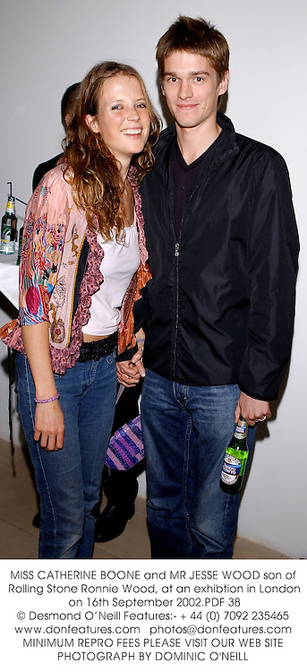 MISS CATHERINE BOONE and MR JESSE WOOD son of Rolling Stone Ronnie Wood, at an exhibtion in London on 16th September 2002.PDF 38