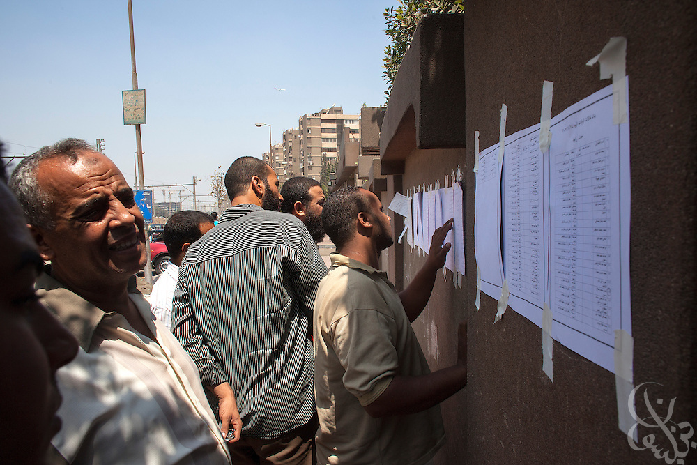 Egyptians look for the names of their relatives on lists of the dead posted August 15, 2014 on the wall of the Health Insurance Hospital in the Nasr City district of Cairo, Egypt.  A day after a violent raid by security forces on the supporters of deposed Egyptian President Mohamed Morsi, the country is trying to come to terms with the news that at least 600 people were killed and thousands more injured across Egypt during the raid on Rabaah al-Adawiya, and another, smaller protest camp in the district of Giza across town.