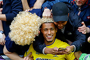 AFC Wimbledon forward Lyle Taylor (33) goes into the AFC Wimbledon fans to appreciate the wigs being worn during the EFL Sky Bet League 1 match between Wigan Athletic and AFC Wimbledon at the DW Stadium, Wigan, England on 28 April 2018. Picture by Simon Davies.
