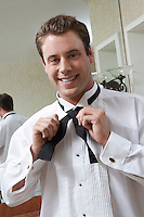 Groom tying bow tie, portrait