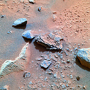 This colour image taken by the Mars Exploration Rover Spirit's panoramic camera on Sol 40 is centred on an unusually flaky rock called Mimi. Mimi is only one of many features in the area known as 'Stone Council,' but looks very different from any rock that scientists have seen at the Gusev crater site so far. Mimi's flaky appearance leads scientists to a number of hypotheses. Mimi could have been subjected to pressure either through burial or impact, or may have once been a dune that was cemented into flaky layers, a process that sometimes involves the action of water.