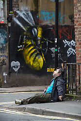 © Licensed to London News Pictures . 06/04/2017 . Manchester , UK . A man appears disorientated and is incoherent as he sits forward on the pavement on Newton Street . An epidemic of abuse of the drug spice by some of Manchester's homeless population , in plain sight , is causing users to experience psychosis and a zombie-like state and is daily being witnessed in the Piccadilly Gardens area of Manchester , drawing large resource from paramedic services in the city centre . Photo credit : Joel Goodman/LNP