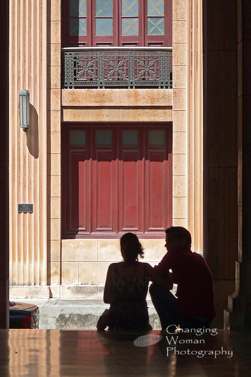 A young couple, students at Havana University, sits in a shaded campus doorway facing the sun-bathed building across the street. Their image, set in the physical space and social context of Cuba's ongoing commitment to its citizens' education, seems emblematic of a bright future, but time and politics will tell.