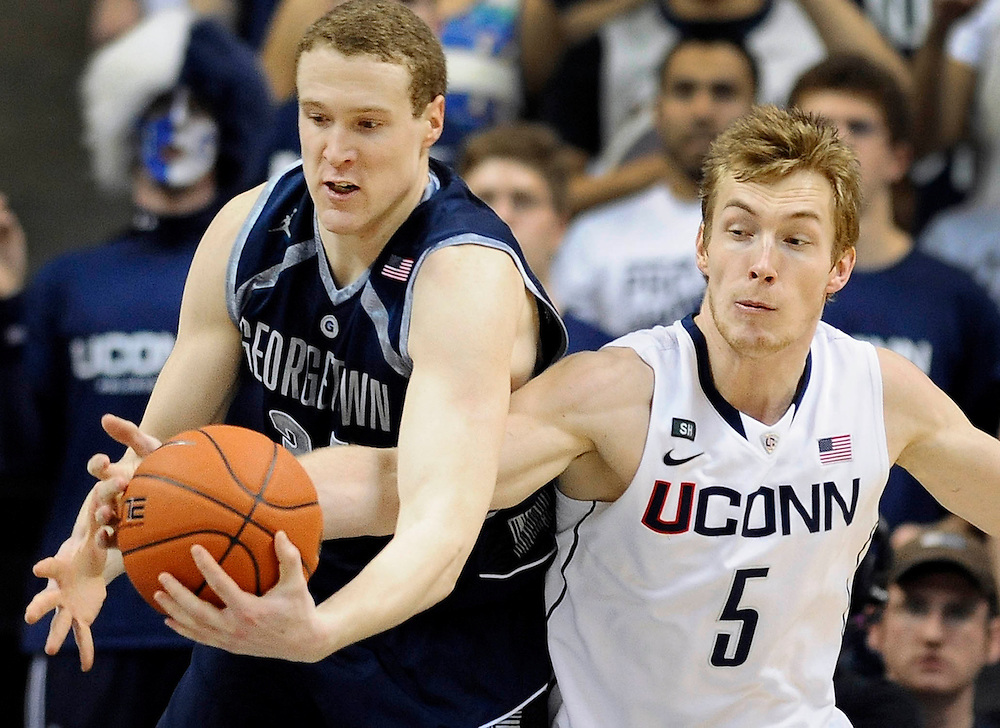 Georgetown's Nate Lubick, left, tangles with Connecticut's Niels Giffey during the first half of an NCAA college basketball game in Storrs, Conn., Wednesday, Feb. 27, 2013. (AP Photo/Jessica Hill)