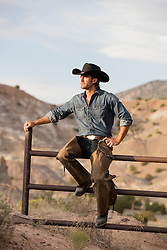 rugged cowboy sitting on a ranch fence