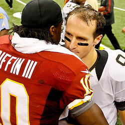September 9, 2012; New Orleans, LA, USA; Washington Redskins quarterback Robert Griffin III (10) talks with New Orleans Saints quarterback Drew Brees (9) following a win at the Mercedes-Benz Superdome. The Redskins defeated the Saints 40-32. Mandatory Credit: Derick E. Hingle-US PRESSWIRE