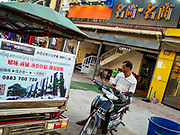 "14 FEBRUARY 2019 - SIHANOUKVILLE, CAMBODIA:  A Cambodian man sits on his motorcycle sandwhiched between a tuk-tuk with a Chinese real estate project and a Chinese shop in Sihanoukville. There are about 80 Chinese casinos and resort hotels open in Sihanoukville and dozens more under construction. The casinos are changing the city, once a sleepy port on Southeast Asia's ""backpacker trail"" into a booming city. The change is coming with a cost though. Many Cambodian residents of Sihanoukville  have lost their homes to make way for the casinos and the jobs are going to Chinese workers, brought in to build casinos and work in the casinos.      PHOTO BY JACK KURTZ"
