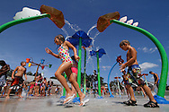 Children play among the colorful features at the new splash pad at Chesley Park in New Britain, CT. (Photo by Kevin Bartram)