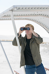 man looking through binoculars in White Sands, New Mexico