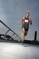 Athlete running on footbridge low angle view Millennium Bridge London England