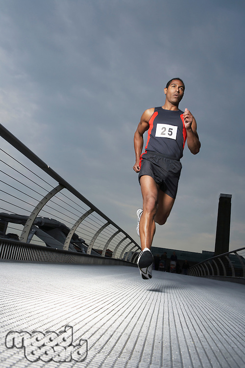 Athlete running on footbridge low angle view Millennium Bridge London England