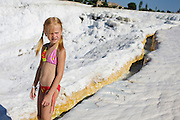 A girl walking down the hill at pamukkale. The hard, white mineral deposits, which from a distance resemble snow, are caused by the high mineral content of the natural spring water which runs down the cliff and congregates in warm pools on the terraces. This is such a popular tourist attraction that strict rules had to be established in order to preserve its beauty, which include the fact that visitors may no longer walk on the terraces. Those who want to enjoy the thermal waters, however, can take a dip in the nearby pool, littered with fragments of marble pillars.