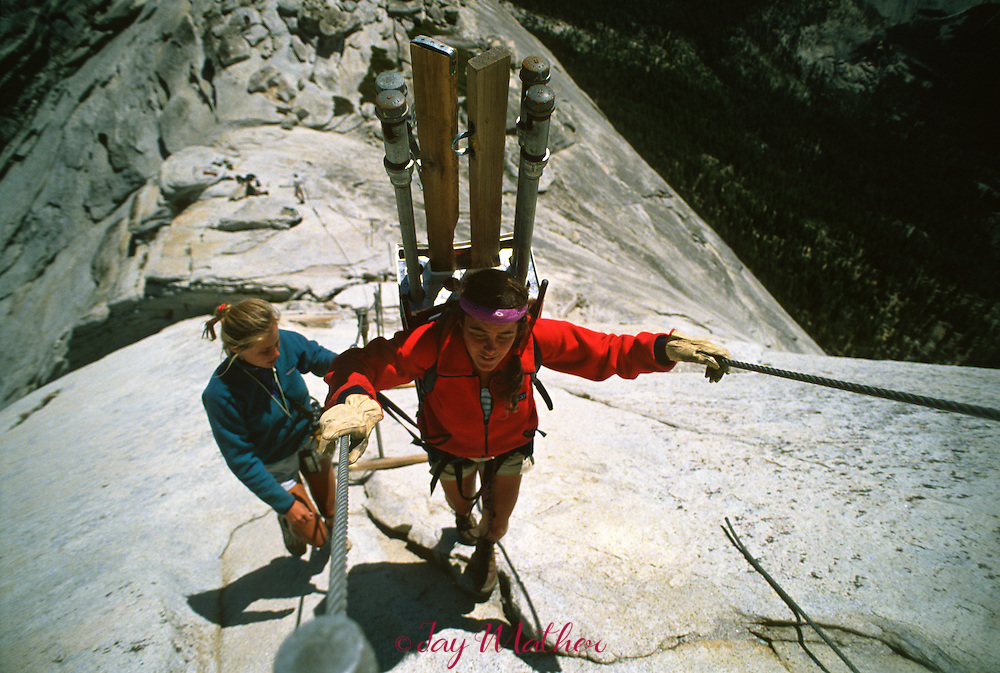 Kim Orr hauls poles and steps up the steep backside of Half Dome.  The trail crew works to install the steel cables and wooden planks that hikers will use to complete the hike to the summit of Half Dome.  The cables are usually installed before Memorial Day each year.  May 1989.
