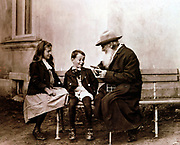Leo Tolstoy (1828-1910) Russian writer, philosopher and mystic, telling his grandchildren a story. Photograph.