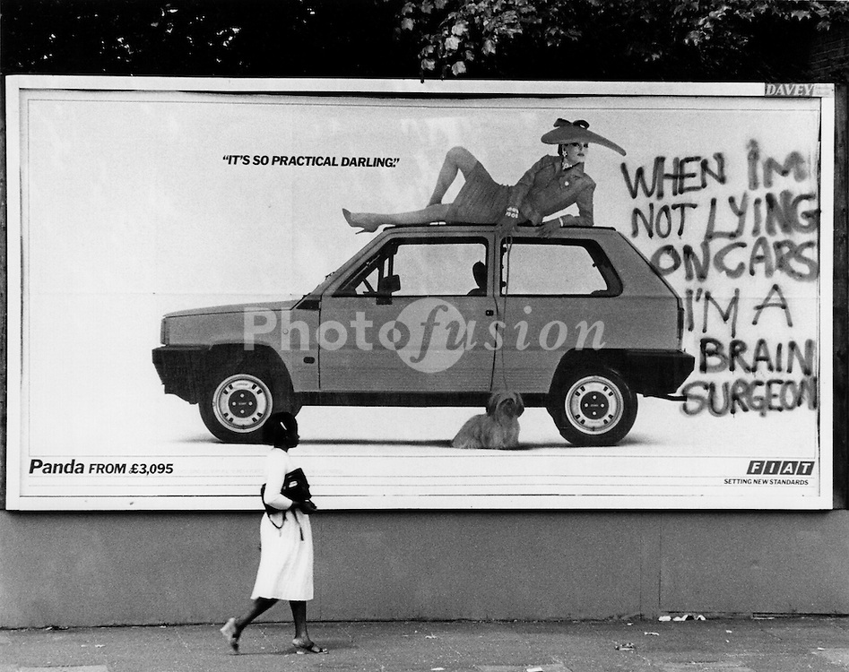Grafitti on sexist car advert Brixton; London UK
