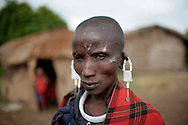 A Maasai woman poses for a portrait while selling jewelry in her village near Ngorongoro Crater in Tanzania, July 7, 2010. (photo by Molly Riley)