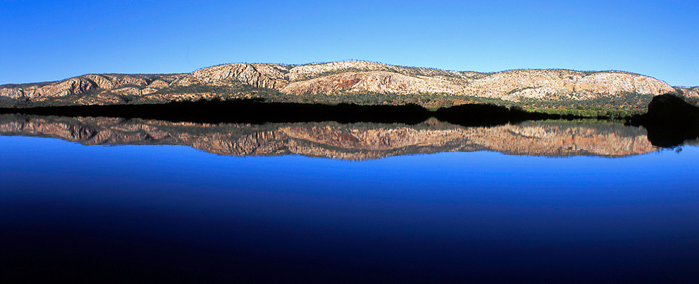 Still water reflects the McLarty Range in Talbot Bay.