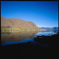The town Bíldudalur mirroring in Arnarfjörður, Western fiords of Iceland. Bíldudalur speglast í Arnarfirðir. Vestfirðir<br />