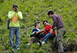 © Licensed to London News Pictures. 27/05/2013. Brockworth, Gloucestershire, UK.  A man (red t-shirt) suffers a serious leg injury during an unofficial race at the annual cheese rolling event.  Police had advised organisers including the local cheese supplier that they might be liable for any mishaps and the event this year was unofficial.  27 May 2013..Photo credit : Simon Chapman/LNP