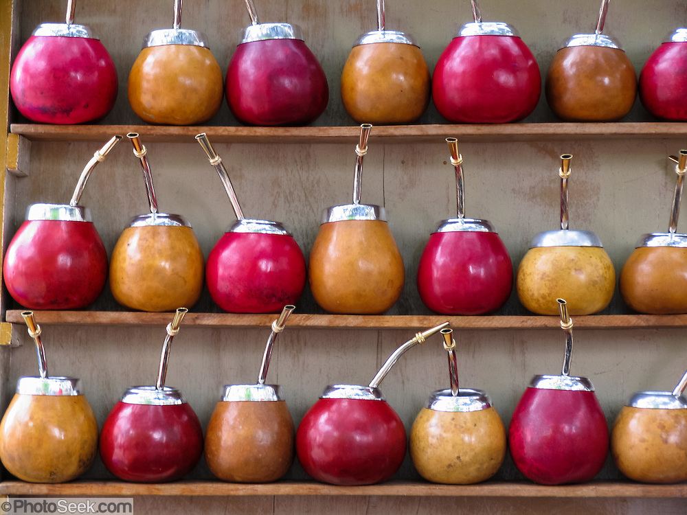 """A vendor shelf offers calabash gourds fitted with silver straws for drinking mate (or maté), the Argentine national drink (known as chimarrão in Portuguese or cimarrón). Mate is prepared by steeping in hot water the dried leaves yerba mate (llex paraguariensis, known in Portuguese as erva-mate), a natural bitter herb. Genetic research on 8000+ year-old archeological calabash seeds (Lagenaria siceraria) found in America suggests that bottle gourds may have been domesticated earlier than food crops and livestock, and, like dogs, were brought by Paleo-Indians into the New World across a then-existing land bridge between Asia and America at the end of the last ice age. Mate was first consumed by the indigenous Guaraní and also spread by the Tupí people that lived in Southern Brazil (Paraguayan territory before the war of the Triple Alliance). European colonizers adopted yerba mate in the Spanish colony of Paraguay in the late 1500s, and in the 1600s, usage spread to the River Plate (Río de la Plata) and onwards to Chile. Buy a traditional mate-drinking gourd at a fun street fair in historic San Telmo (""""Saint Pedro González Telmo""""), the oldest neighborhood (barrio) in Buenos Aires, Argentina, South America. Published 2013 in JSE magazine issue #54 in A5 size by Highbury Safika Media, Roggebaai, Cape Town, South Africa."""