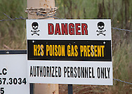 Warning sign at a  New Dominion fracking industry in Wellson Oklahoma. The sign should say warning H2S gas 'may' be present, not that it is present.